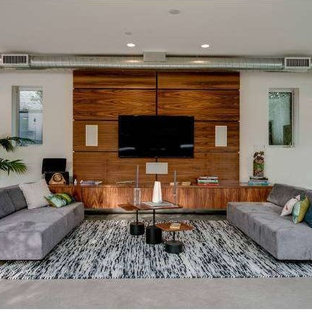 Inspiration for a mid-sized modern open concept home theatre in Los Angeles with white walls, concrete floors and a wall-mounted tv.
