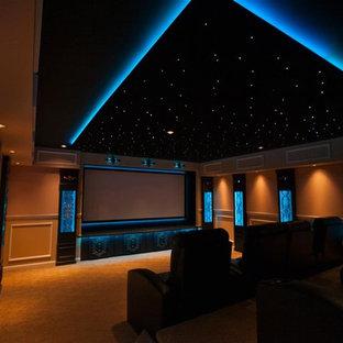 グランドラピッズの広いトラディショナルスタイルのおしゃれな独立型シアタールーム (ベージュの壁、カーペット敷き、プロジェクタースクリーン、オレンジの床) の写真