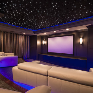 Large trendy enclosed carpeted and gray floor home theater photo in Atlanta with gray walls and a projector screen