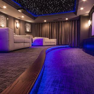 Ejemplo de cine en casa cerrado, actual, grande, con paredes grises, moqueta, pantalla de proyección y suelo gris