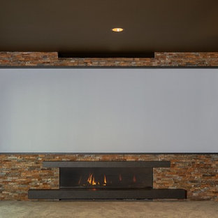 Example of a large mountain style open concept carpeted and beige floor home theater design in Seattle with green walls and a projector screen