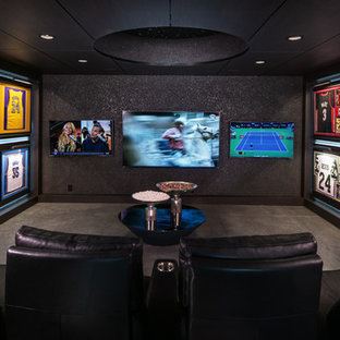 Photo of an industrial enclosed home theatre in Omaha with black walls, concrete floors, a wall-mounted tv and grey floor.