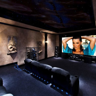 Example of a huge minimalist enclosed carpeted and blue floor home theater design in Atlanta with beige walls and a projector screen