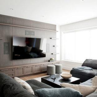 Immagine di un home theatre tradizionale di medie dimensioni e aperto con pareti bianche, pavimento in legno massello medio, TV a parete e pavimento marrone