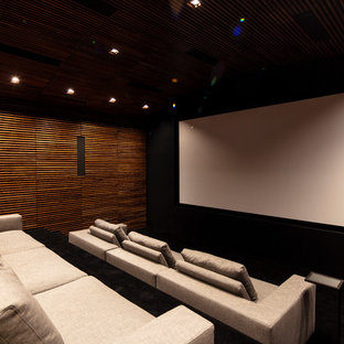 Expansive modern enclosed home theatre in Los Angeles with black walls, a projector screen and black floor.