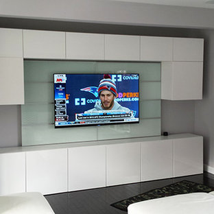 Design ideas for a mid-sized modern enclosed home theatre in Boston with a built-in media wall, grey walls, dark hardwood floors and black floor.