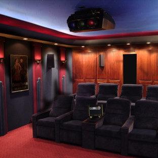 Idee per un home theatre classico di medie dimensioni e chiuso con pareti nere, moquette e schermo di proiezione