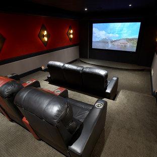 Idee per un home theatre tradizionale chiuso e di medie dimensioni con pareti rosse, moquette e schermo di proiezione