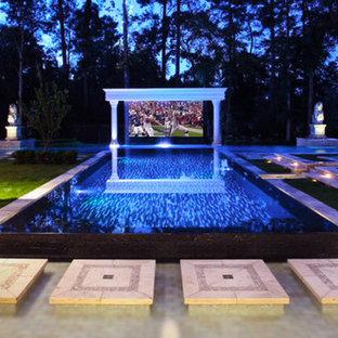 Esempio di un ampio home theatre tropicale aperto con pavimento in terracotta e schermo di proiezione