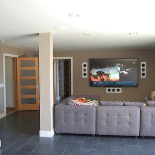 Mittelgroßes, Offenes Heimkino mit beiger Wandfarbe, Schieferboden und Wand-TV in Los Angeles