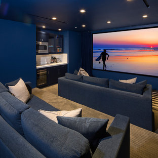 Photo of a beach style enclosed home theatre in Los Angeles with blue walls, carpet, a projector screen and grey floor.