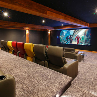 Inspiration for a large rustic enclosed carpeted and blue floor home theater remodel with brown walls and a projector screen