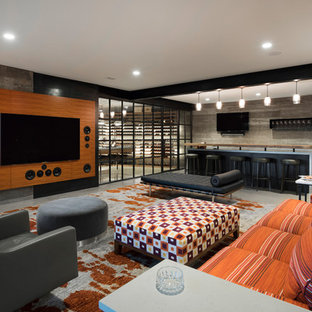 This is an example of a country home theatre in Minneapolis with a wall-mounted tv, grey floor and concrete floors.