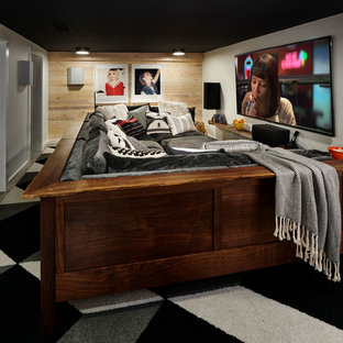 This is an example of a small bohemian enclosed home cinema in Portland with white walls, concrete flooring, a wall mounted tv and grey floors.