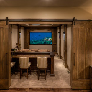 Design ideas for an expansive transitional enclosed home theatre in Salt Lake City with beige walls, carpet, a wall-mounted tv and beige floor.