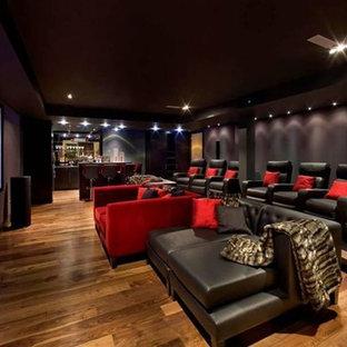 Esempio di un ampio home theatre minimalista aperto con pareti viola, pavimento in legno massello medio e schermo di proiezione
