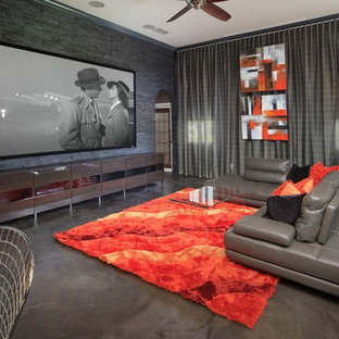 Large contemporary open concept home theatre in Orlando with grey walls, a projector screen, concrete floors and grey floor.