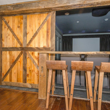 Rustic finished basement with theater room, rustic sliding barn doors