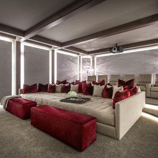 Imagen de cine en casa cerrado, actual, grande, con paredes grises, moqueta, pantalla de proyección y suelo gris