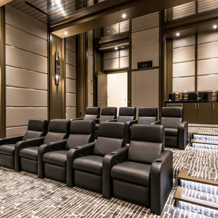 Photo of a large contemporary enclosed home theatre in Las Vegas with carpet, a projector screen, grey walls and grey floor.