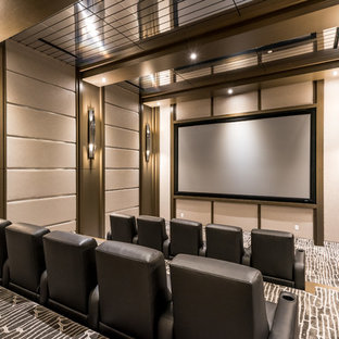 Large contemporary enclosed home theatre in Las Vegas with carpet, a projector screen, grey walls and grey floor.