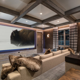 Example of a mountain style carpeted and gray floor home theater design in Other with brown walls and a wall-mounted tv