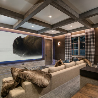 Example of a mountain style enclosed carpeted and gray floor home theater design in Other with brown walls and a projector screen