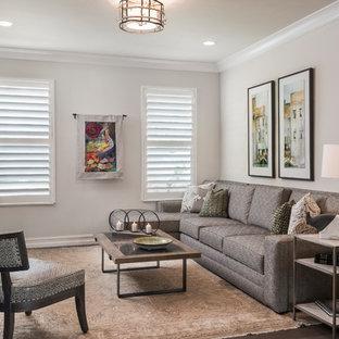 Modelo de cine en casa abierto, clásico renovado, de tamaño medio, con paredes grises, suelo de madera en tonos medios, televisor colgado en la pared y suelo marrón