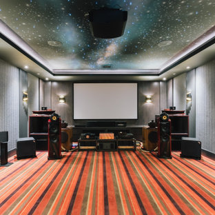 This is an example of a large modern enclosed home theatre in Vancouver with grey walls, carpet, a projector screen and multi-coloured floor.