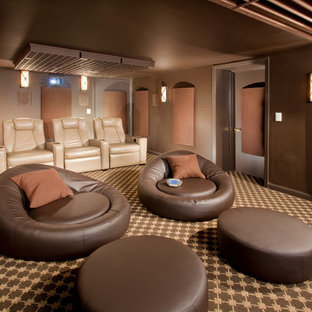 Home theater - mid-sized modern enclosed carpeted home theater idea in Newark with brown walls and a projector screen