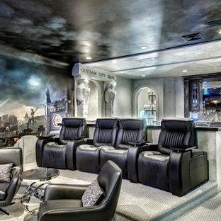 Foto di un grande home theatre bohémian aperto con pareti grigie, moquette, schermo di proiezione e pavimento grigio