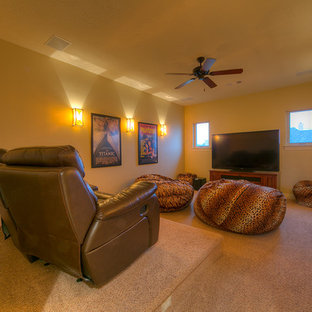 Example of a mid-sized mountain style enclosed carpeted home theater design in Houston with yellow walls and a wall-mounted tv