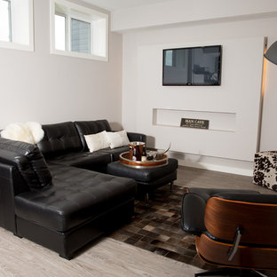 This is an example of a small modern open concept home theatre in Calgary with grey walls, vinyl floors and a wall-mounted tv.