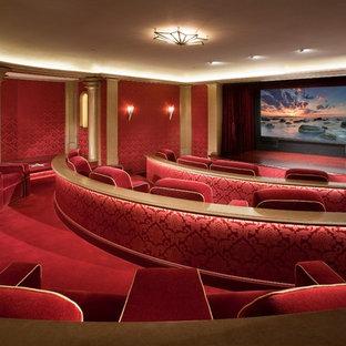 Inspiration pour une grande salle de cinéma victorienne fermée avec un mur rouge, moquette, un écran de projection et un sol rouge.