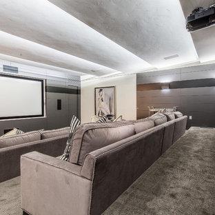 Réalisation d'une très grande salle de cinéma style shabby chic fermée avec un mur gris, moquette, un écran de projection et un sol gris.