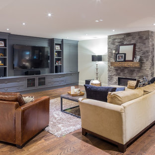 This is an example of a large transitional open concept home theatre in Toronto with grey walls, dark hardwood floors and a built-in media wall.