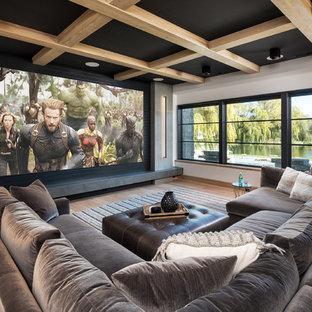 Aménagement d'une grande salle de cinéma contemporaine ouverte avec un mur blanc, un sol en bois brun, un écran de projection et un sol marron.