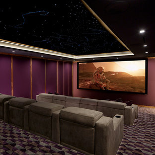 Classic enclosed home cinema in New York with purple walls, carpet, a projector screen and multi-coloured floors.