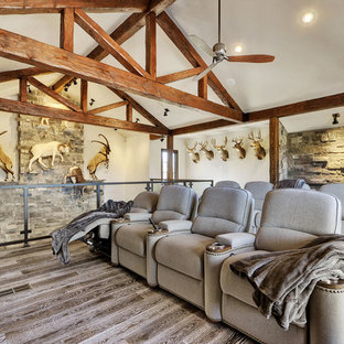 Example of a mid-sized mountain style open concept medium tone wood floor home theater design in Austin with gray walls