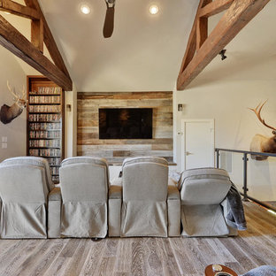 Home theater - mid-sized rustic open concept medium tone wood floor home theater idea in Austin with gray walls and a wall-mounted tv