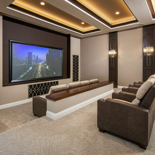 Large traditional open plan home cinema in Omaha with carpet, beige walls, a projector screen and beige floors.