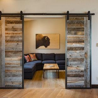 Foto di un piccolo home theatre contemporaneo chiuso con pareti beige, pavimento in legno massello medio, TV a parete e pavimento beige