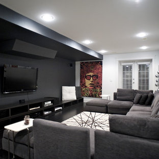 Trendy black floor home theater photo in Vancouver with black walls and a wall-mounted tv