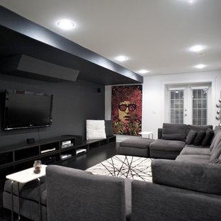 Ejemplo de cine en casa actual con paredes negras, televisor colgado en la pared y suelo negro