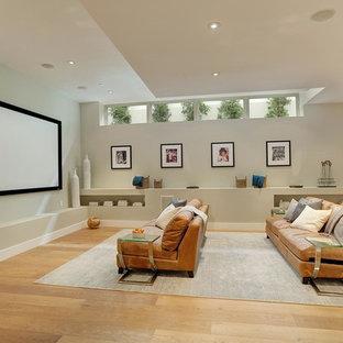 Ejemplo de cine en casa abierto, minimalista, grande, con paredes grises, suelo de madera en tonos medios y pantalla de proyección