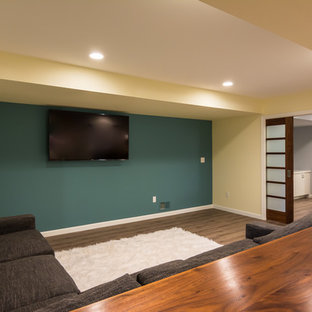 Large transitional open concept home theatre in Detroit with yellow walls, vinyl floors, a wall-mounted tv and brown floor.