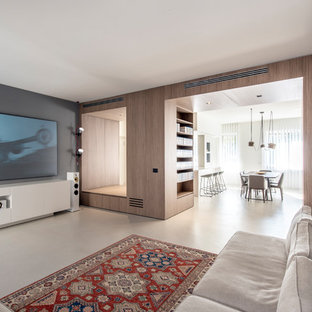 Large contemporary open plan home cinema in Milan with grey walls, concrete flooring, grey floors and a wall mounted tv.
