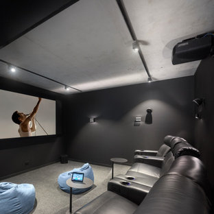 Design ideas for a contemporary enclosed home theatre in Brisbane with black walls, carpet, a projector screen and grey floor.