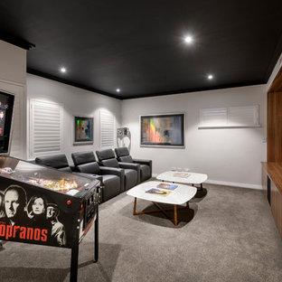 Imagen de cine en casa cerrado, actual, con paredes grises, moqueta, pared multimedia y suelo gris