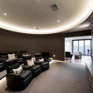 Photo of a contemporary enclosed home theatre in Melbourne with brown walls, carpet, a wall-mounted tv and grey floor.